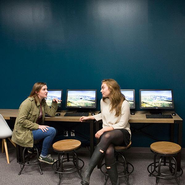 women talking by computers