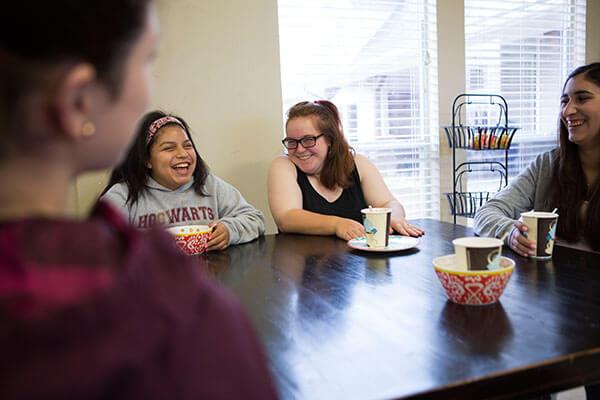 women laughing around table