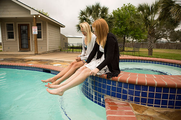 two girls dipping their feet in the pool